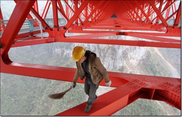 Worker getting bridge ready for the Official opening. (With a broom?)